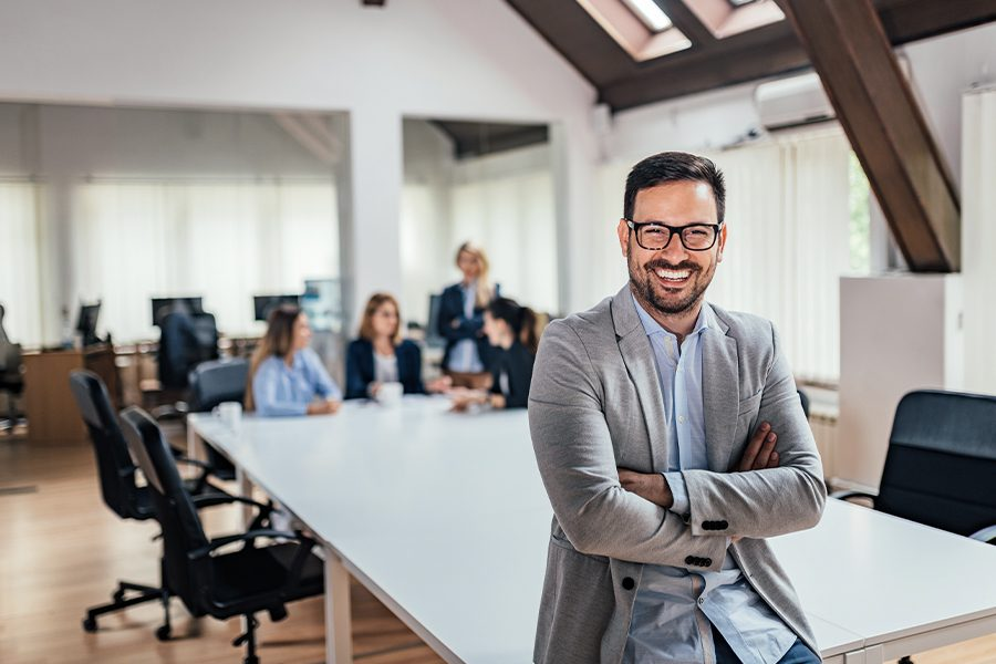 Business Insurance - Portrait of Businessman Sitting on the Edge of Conference Table and Looking at Camera with Colleagues Working Behind Him and Blurred in the Background
