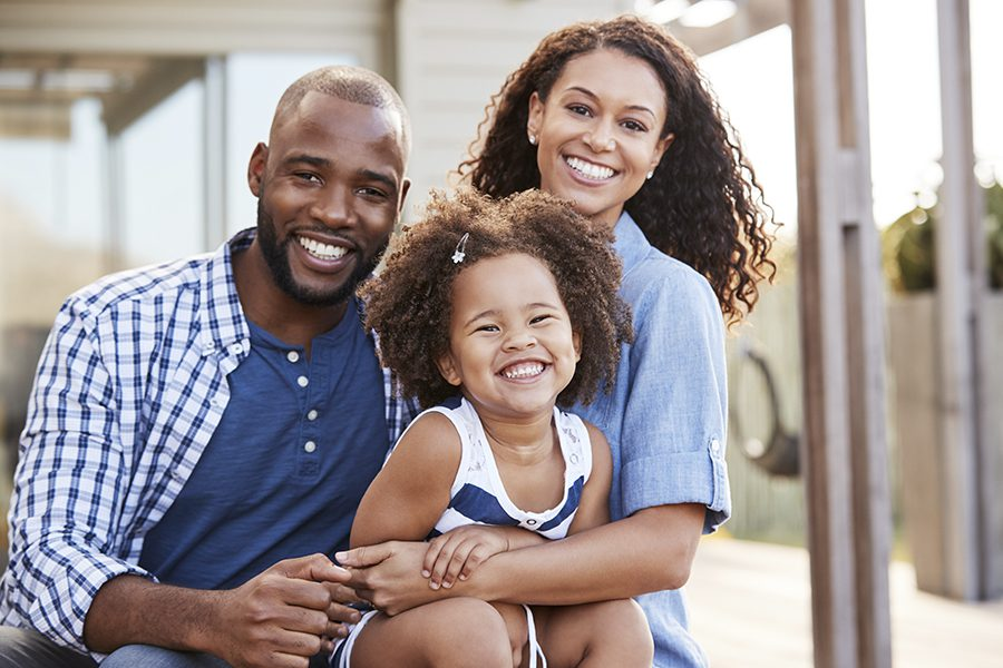 Personal Insurance - Young Family Embracing While Sitting Outside of Their Home and Smiling at Camera
