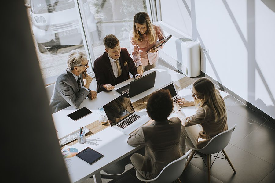Our Story - View of Group of Employees Working Together in a Modern Office