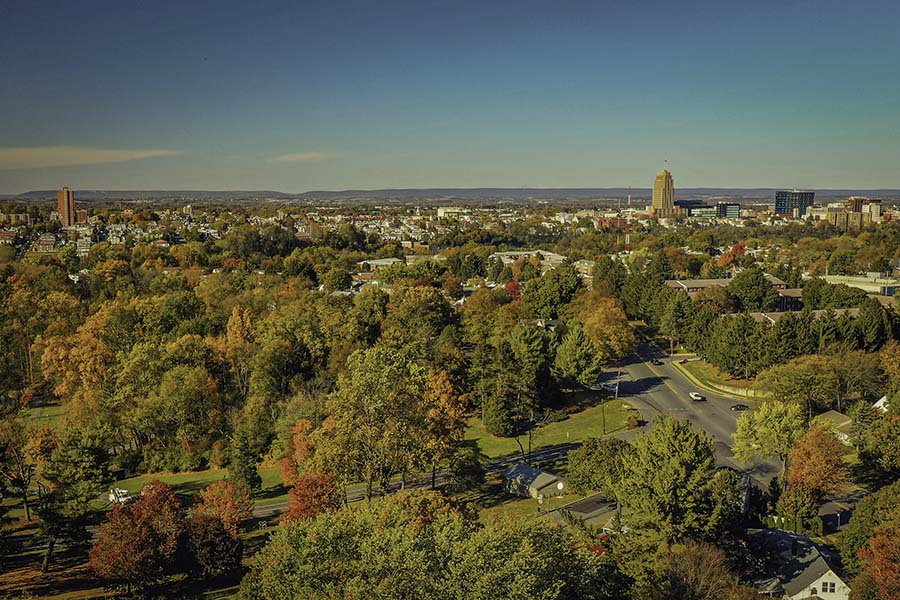 Allentown PA - Aerial View of the City of Allentown in Pennsylvania Against a Blue Sky Surrounded by Green Foliage