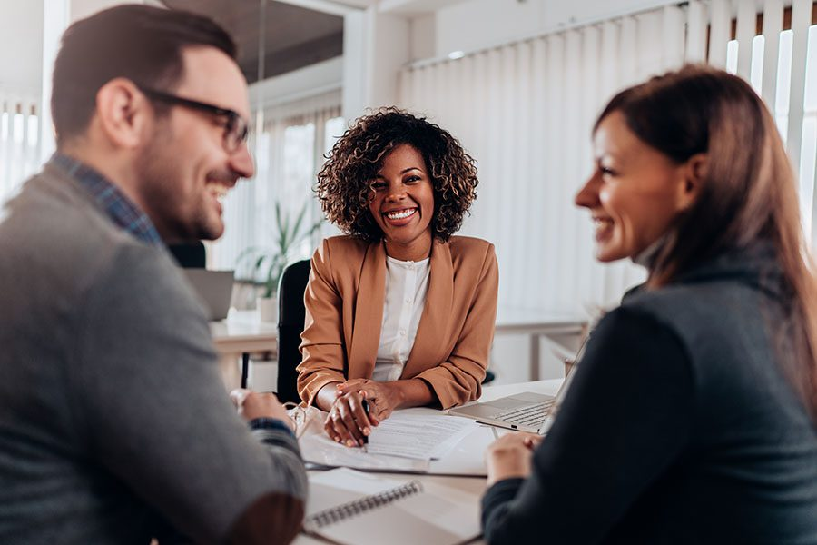 Business Insurance - View of a Smiling Financial Advisor Meeting with a Cheerful Young Couple in Her Office