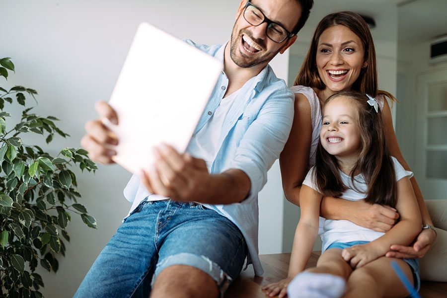 Client Center - Portrait of a Cheerful Family with a Young Daughter Sitting at Home Using a Tablet