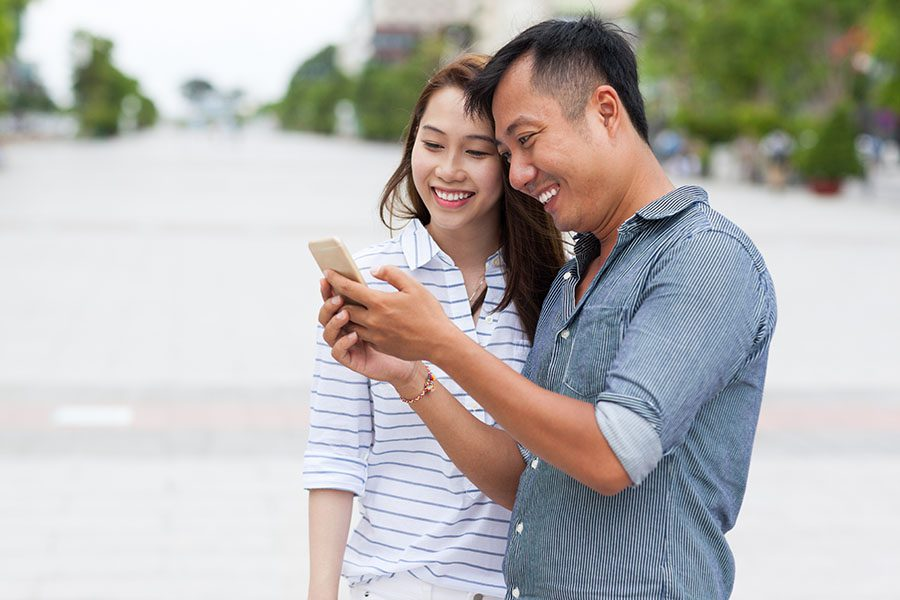 Resources - Closeup Portrait of a Smiling Young Couple Using a Cellphone While Standing Outside in the City