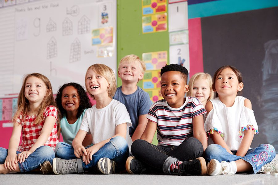 Specialized Business Insurance - View of Group of Smiling Diverse Children Sitting on the Floor in the Classroom