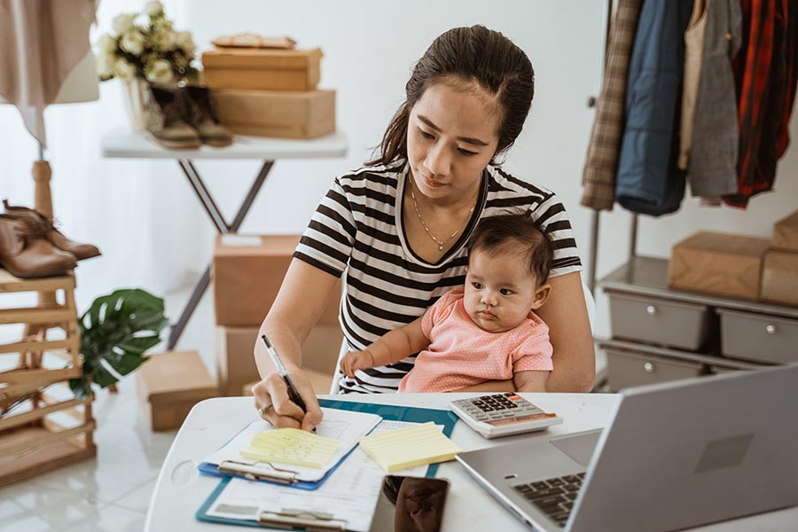 Client Center - Mother With Baby on Her Lap Takes Notes While Using a Laptop in Her Studio