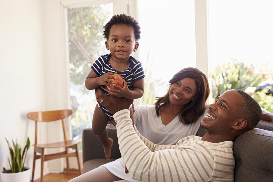 Personal Insurance - Father Lifts His Toddler Son up, Mother Smiling at Them, All Sitting on Their Couch in Their Sunny Living Room
