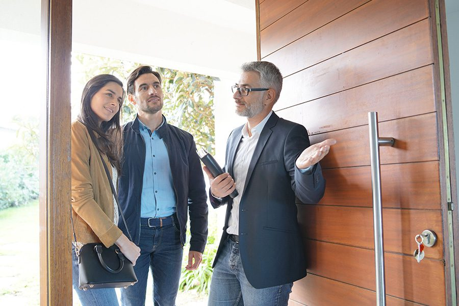 Business Insurance - Property Manager Showing Young Couple New Modern High End Home