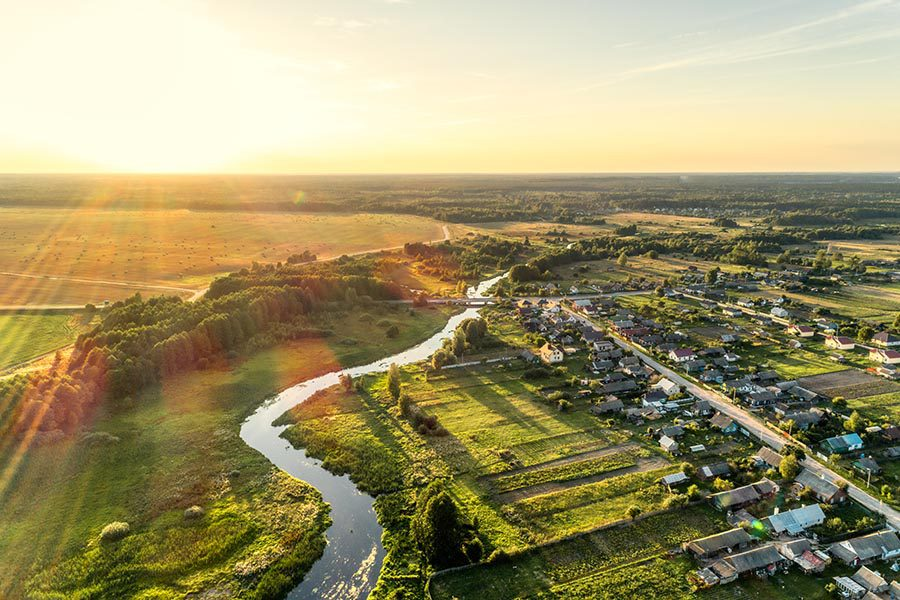 About Our Agency - Aerial Landscape of a Suburban and Rural Area With a Small River Cutting Through