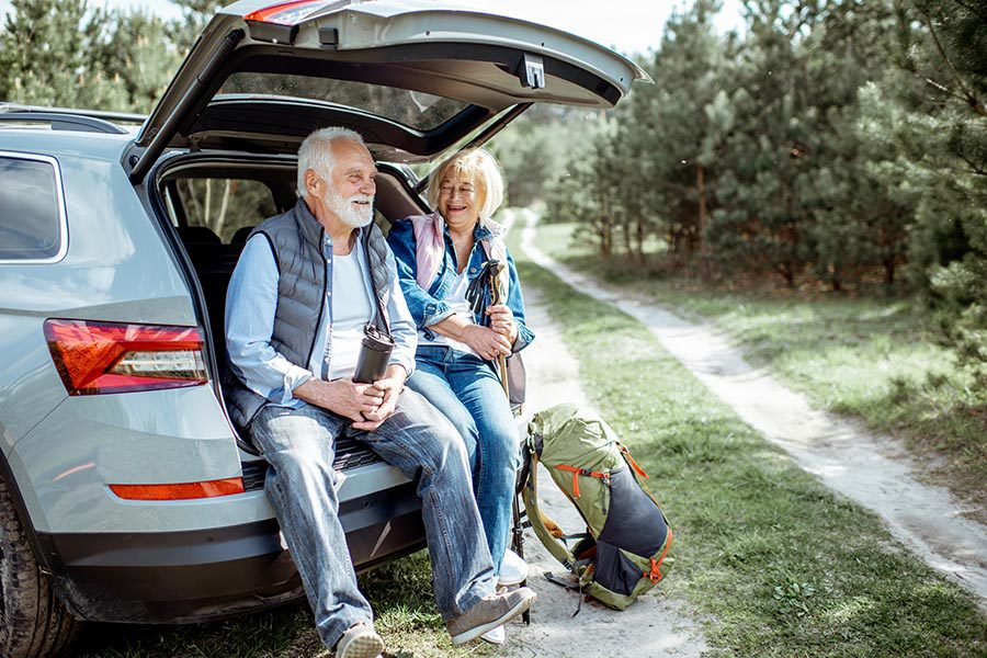 Contact Us - Senior Couple Sits in the Back of Their Car's Hatch, Stopping Along a Trail for Some Snacks, Dressed for Autumn Weather