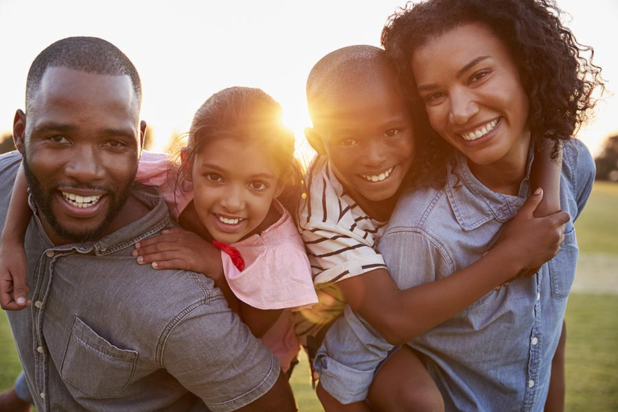 Personal Insurance - Father, Mother and Two Small Kids on Their Backs, Smiling and Standing in Their Yard, Sun Shining