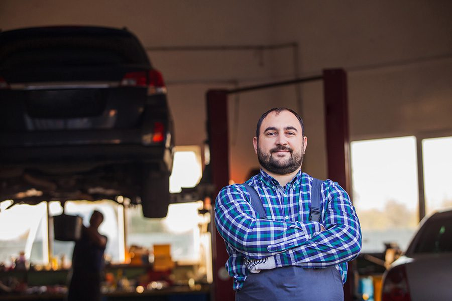 Business Insurance - Portrait of a Small Business Owner Standing in His Garage Repair Shop with His Arms Folded with Views of a Mechanic Working on a Car Repair in the Background