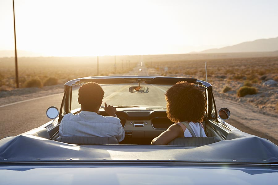 About Our Agency - Couple Cruising In Their Convertible On a Dessert Road at Dusk