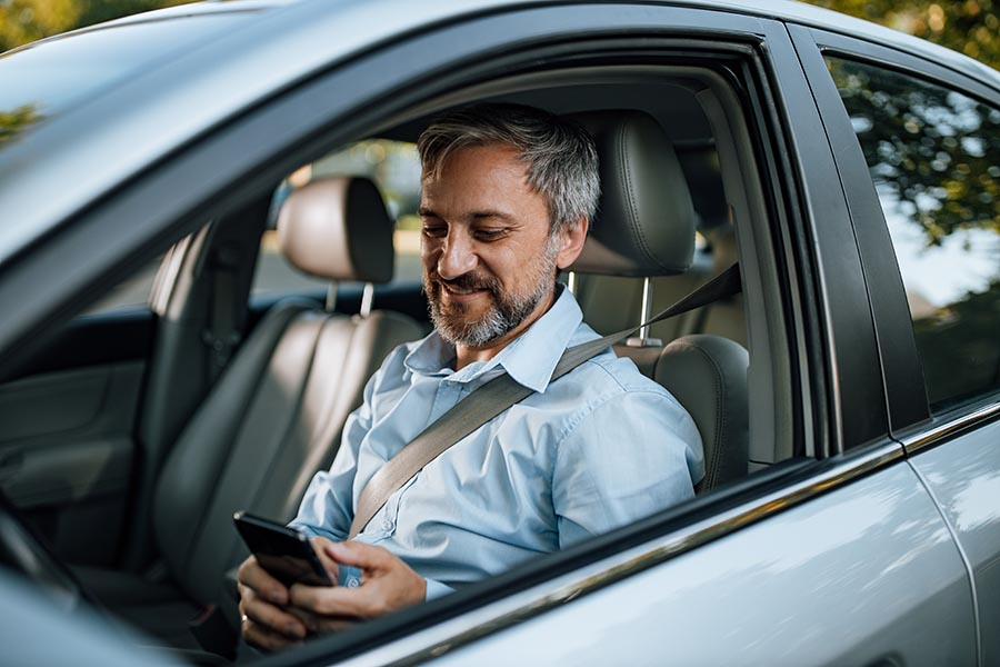 Client Center - Man in a Button Down Shirt With Graying Hair Smiles as He Uses a Smartphone in His Silver Car
