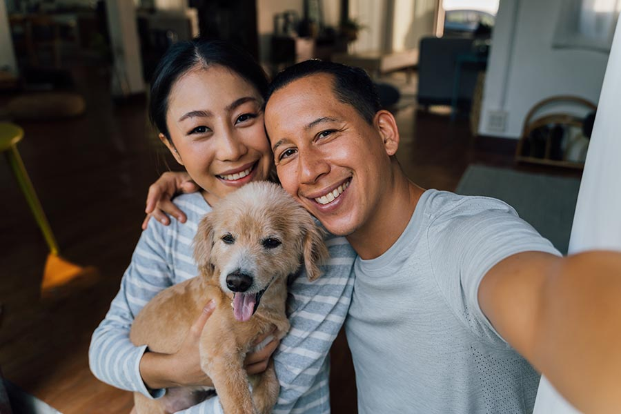 Contact Us - Happy Couple Takes a Selfie With Their Golden Retriever Puppy