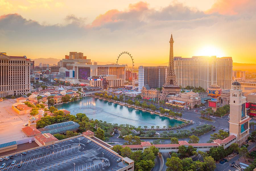 Las Vegas, NV Insurance - Sunset View of the Las Vegas Strip, A Large Pool Surrounded By Palm Trees in the Foreground