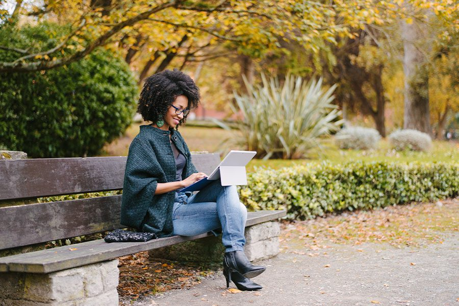 Client Center - Young Woman Working with Laptop Outdoors in a City Park in Autumn
