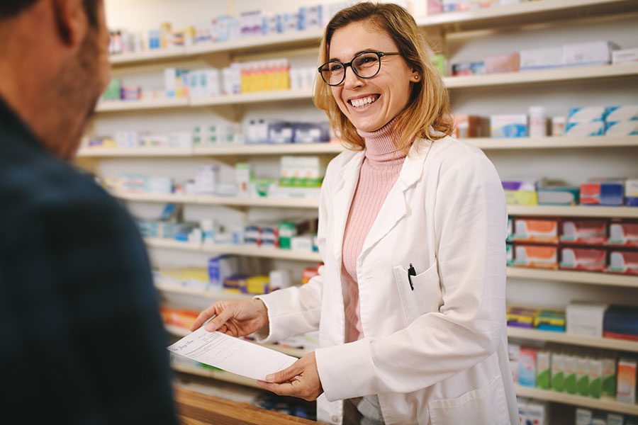 Pharmacy Insurance Network - Helpful Pharmacist Dealing with a Customer