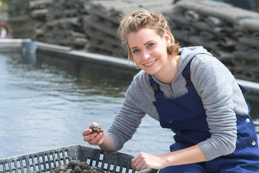 Shellfish Farm Insurance - Happy Female Worker at a Fish and Mussel Farm