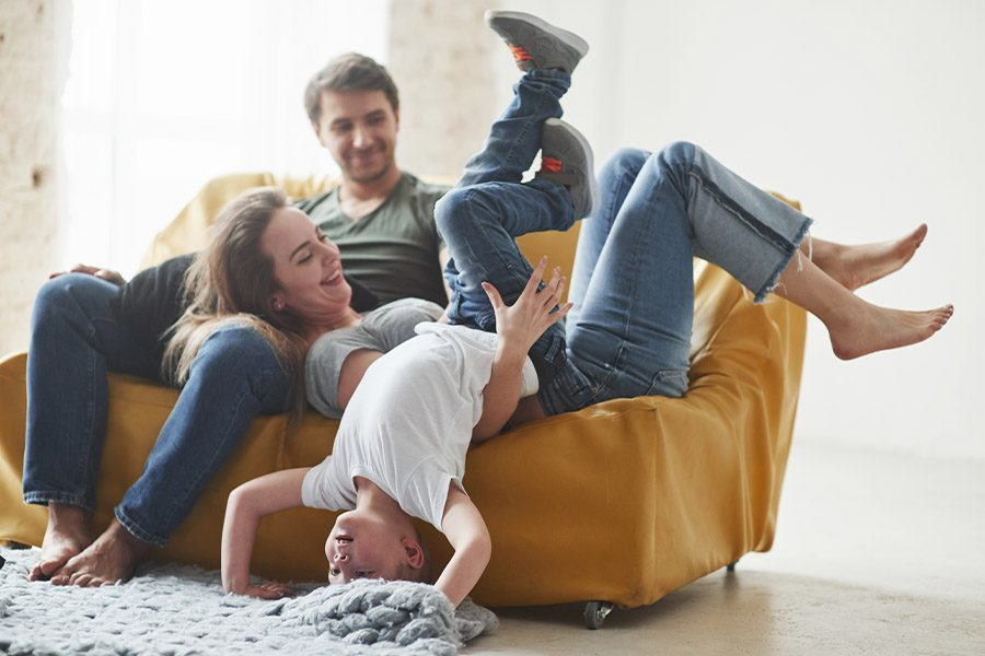 Personal Insurance - Family Having Fun on Small Coach in the Living Room of New Home