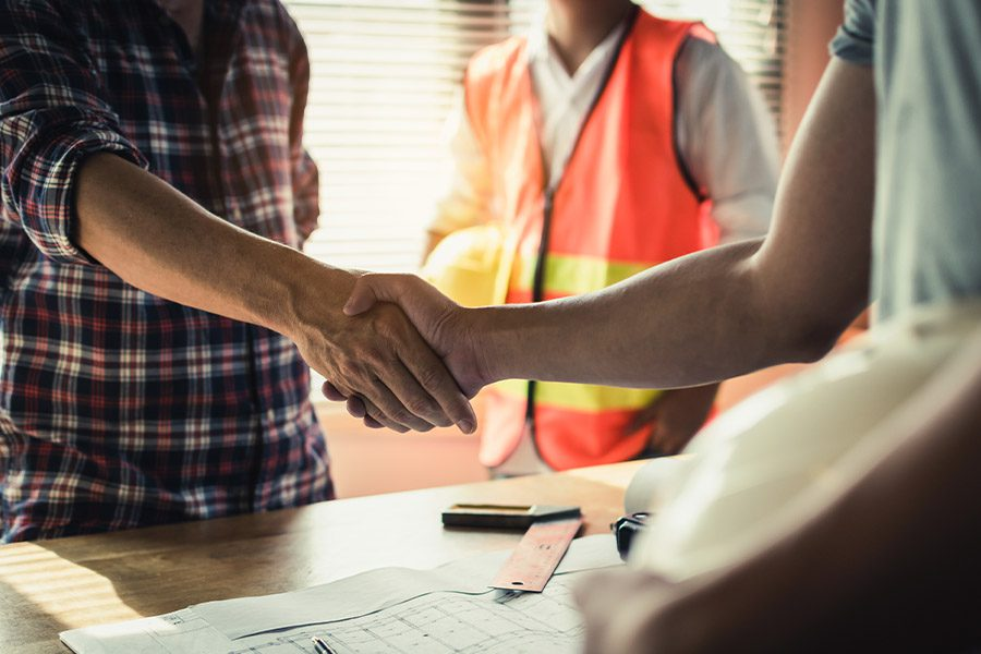 Specialized Business Insurance - Closeup of Contractors and Engineer Shaking Hands in an Office
