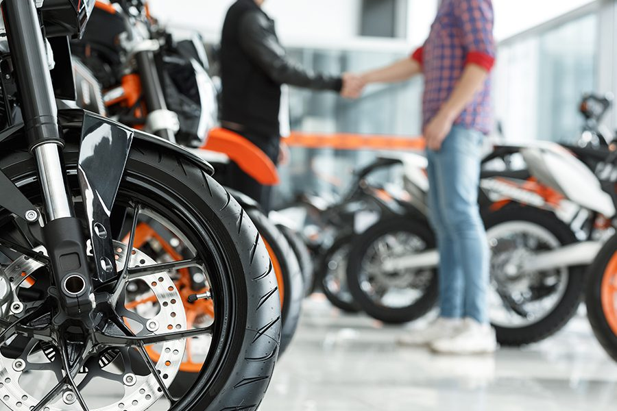 Motorcycle Dealership Insurance - Focus on a Motorcycle Wheel with Male Customer Shaking Hands with Motorcycle Dealership Manager in the Background