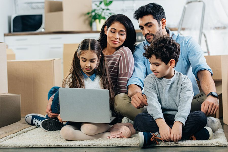 Client Center - Portrait of a Cheerful Family with Two Young Kids Sitting on a Rug in the Living Room While Using a Laptop