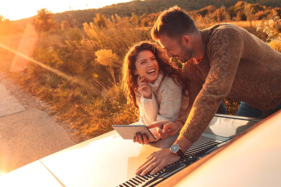 Insurance Quote - Portrait of a Cheerful Young Couple Using a Tablet While Leaning Over the Front Hood of Their Car Along a Countryside Road at Sunset