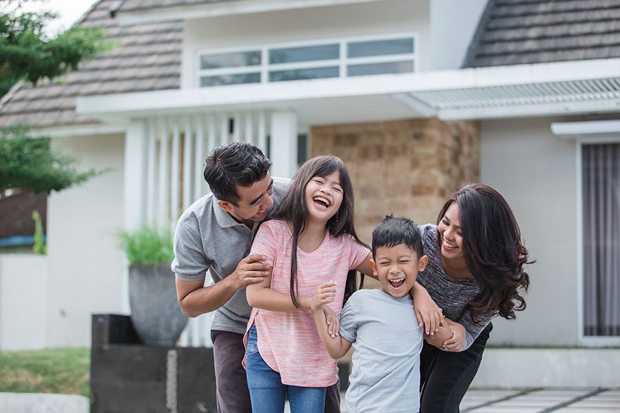 Personal Insurance - Portrait of a Cheerful Family with Two Kids Having Fun Playing Outside Their New Home