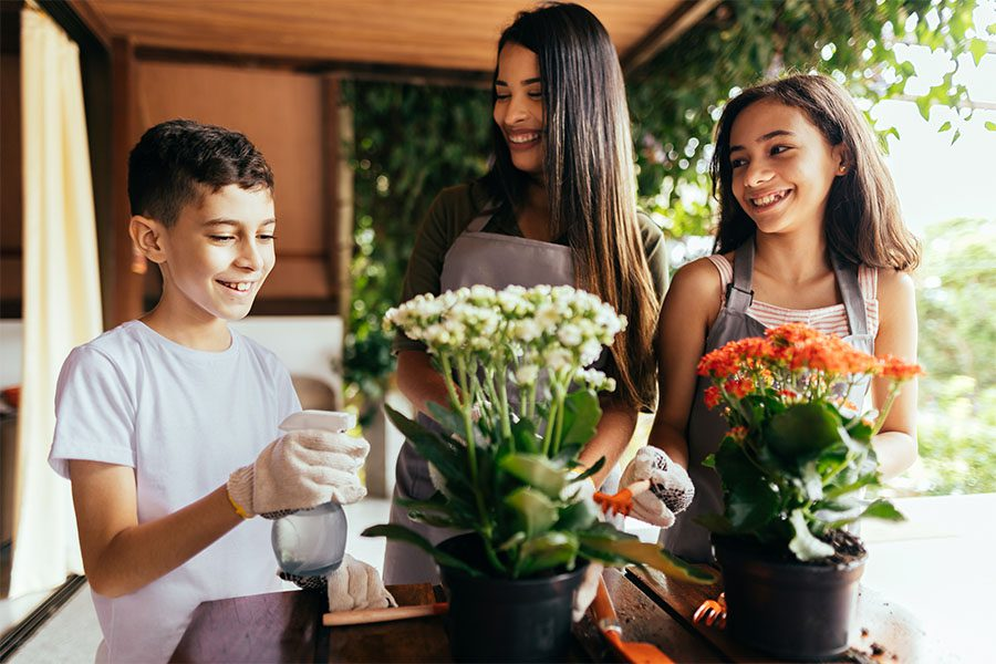 About Our Agency - Portrait of a Young Mother and Her Two Kids Having Fun Spending Time Together Outside on the Deck in the Backyard While Taking Care of Flowers