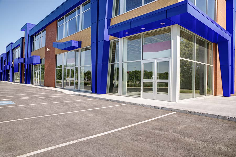Business Insurance - View of an Empty Modern Commercial Office Building Ready for Lease with an Empty Parking Lot in Front