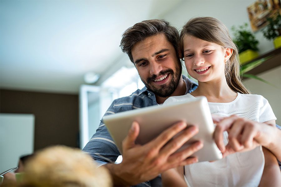 Client Center - Closeup Portrait of a Cheerful Father and Daughter Spending Time Together at Home Using a Tablet