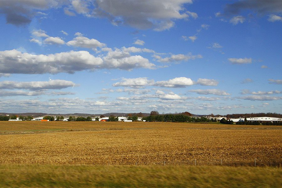 Contact - View of Wheat Farm Field in the Countryside of Lancaster Ohio Against a Bright Blue Cloudy Sky