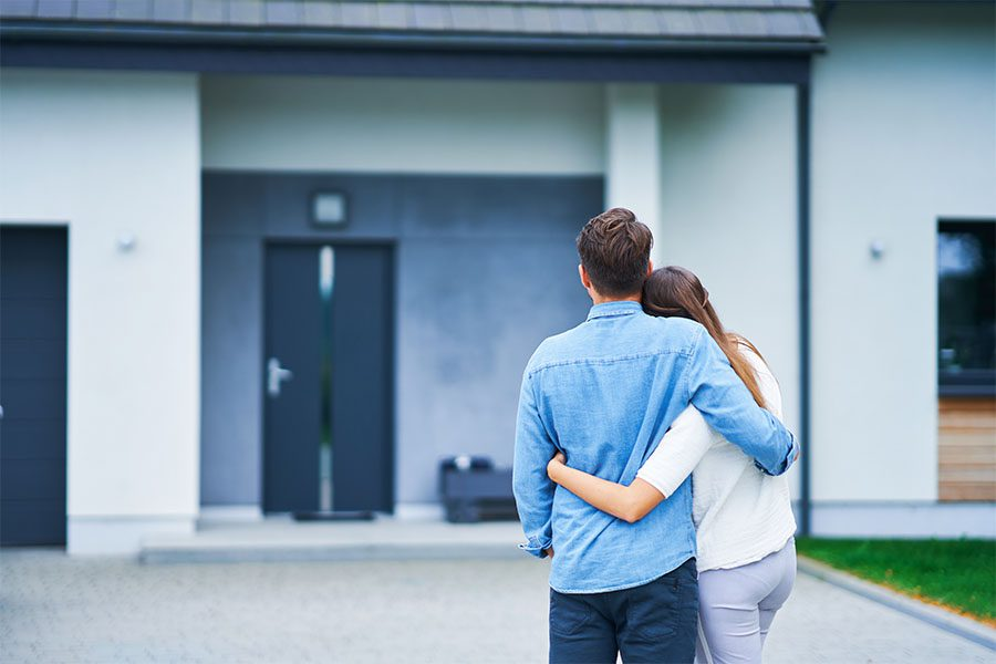 Insurance Quote - Back View of a Young Couple Hugging Each Other While Standing Outside Looking at Their New Home