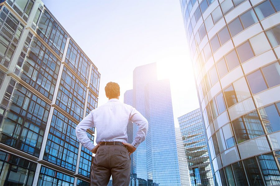 Business Insurance - Rear View of a Business Man Standing in the Middle of Tall Modern Skyscrapers in the City Admiring the View