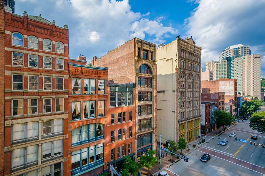 Contact - Row of Colorful Commercial Buildings in Downtown Pittsburgh Pennsylvania Against a Cloudy Blue Sky
