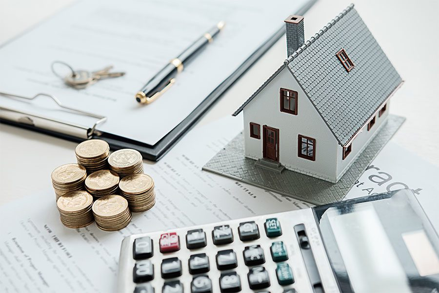 Home Warranty - View of a Model House Sitting on a Table on Top of a Mortgage Application Next to a Stack of Coins a Calculator and a Notepad with Keys and a Contract