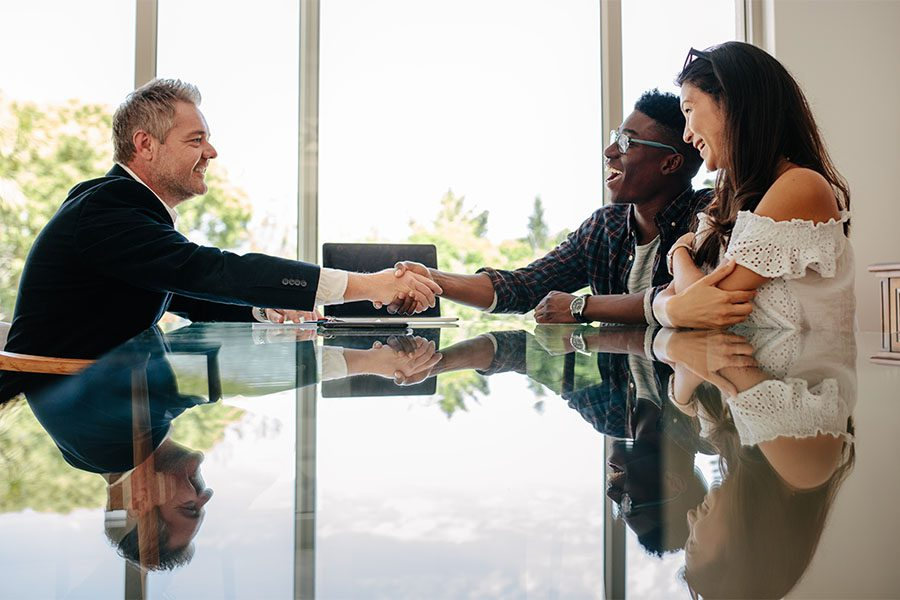 About Our Agency - View of a Realtor Sitting in a Modern Office with a Young Couple Shaking Their Hands to Celebrate Success in Finding a New Home