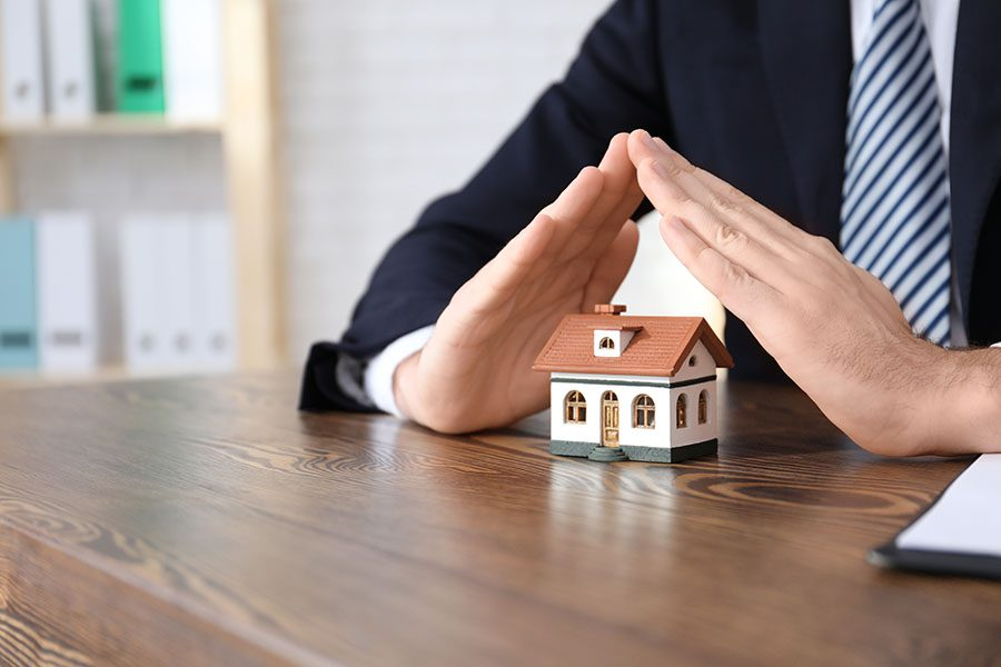 Direct to Consumer Home Warranty - Closeup Portrait of an Insurance Agent Sitting in an Office Holding His Hands Over a Small Toy Model House