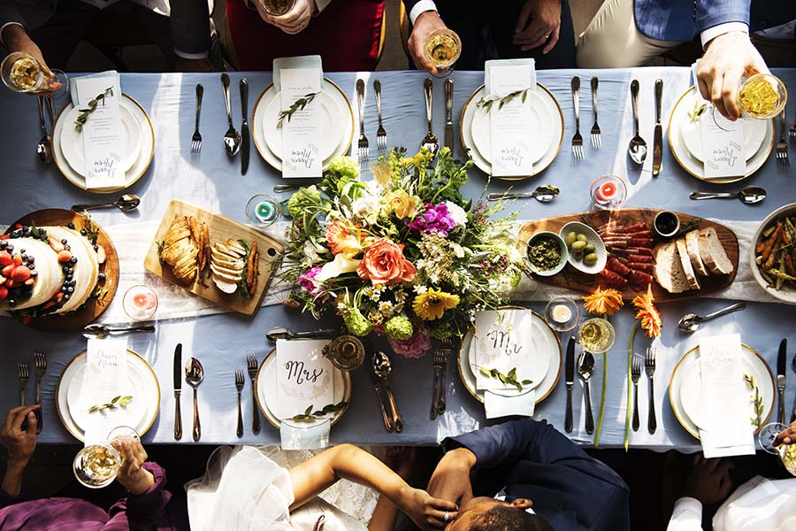 Specialty Lines - Aerial View of a Bride and Groom Kissing While Their Wedding Guests Sit Around a Table Decorated with Flowers and Food