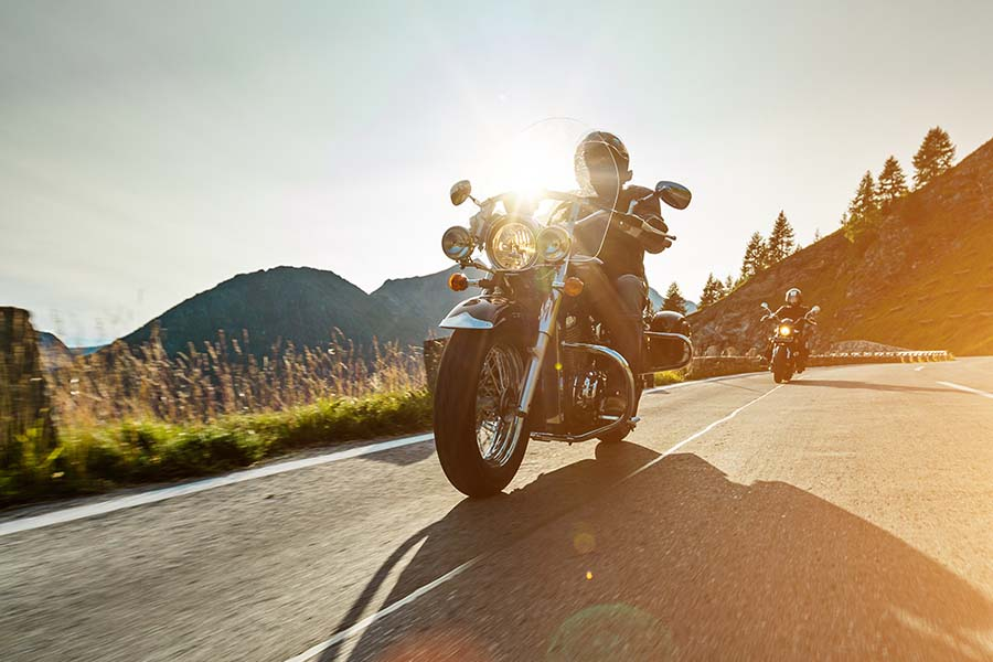 Toys Insurance - View of Two Men Riding Their Motorcylces on a Scenic Road Surrounded by Mountains at Sunset