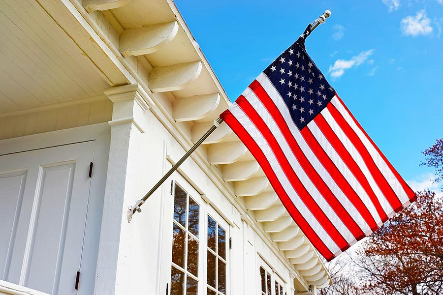 About Our Agency - American Flag Waving On the Front Porch of a White Home on a Sunny Day