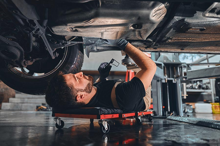 Business Insurance - Young Mechanic Working On the Underside of a Car, Wearing Overalls