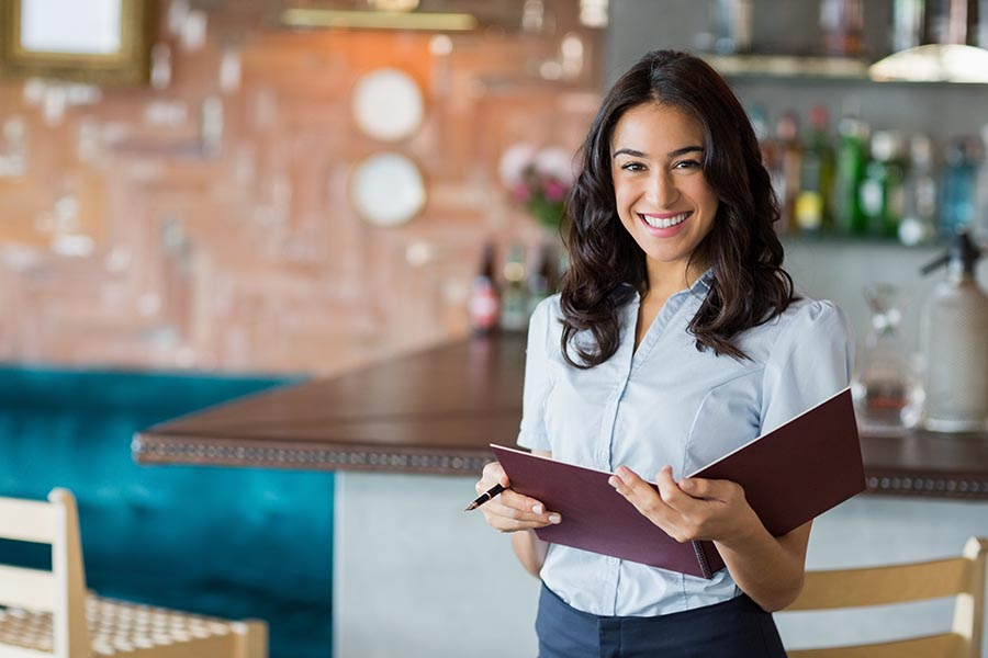 Specialized Business Insurance - Proud Restaurant Owner Holds a Reservation Book, Standing By a Modern Bar
