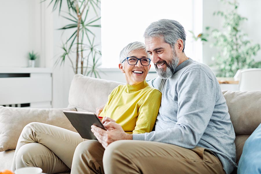 Client Center - Senior Couple Laugh as Their Use a Tablet on Their Couch in Their White Living Room Filled With Plants