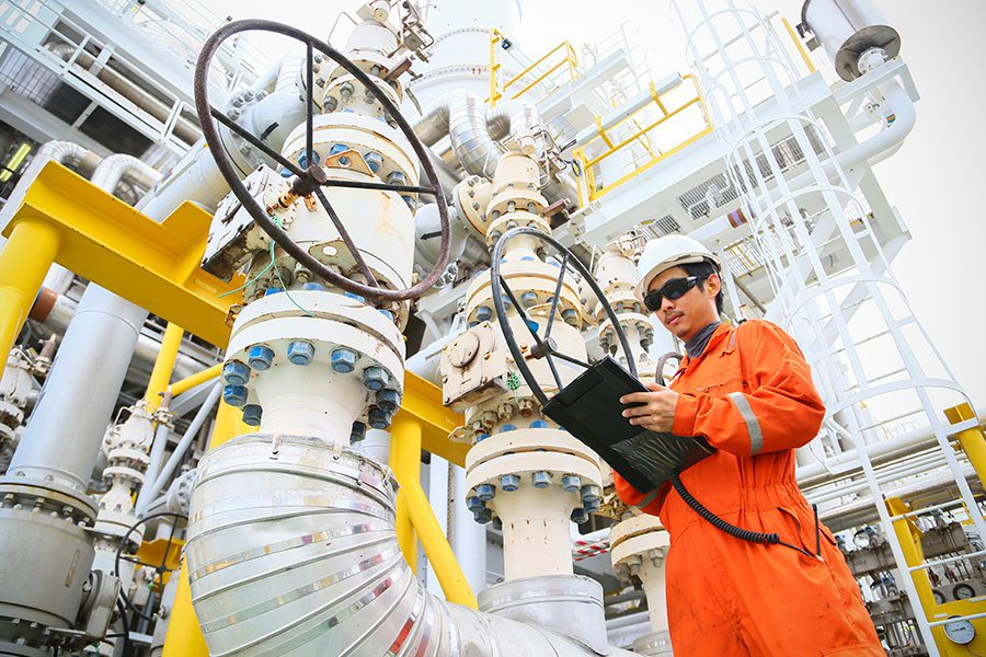 Oil and Gas Insurance - Operator Recording Oil and Gas Process at an Offshore Oil and Gas Rig in the Ocean