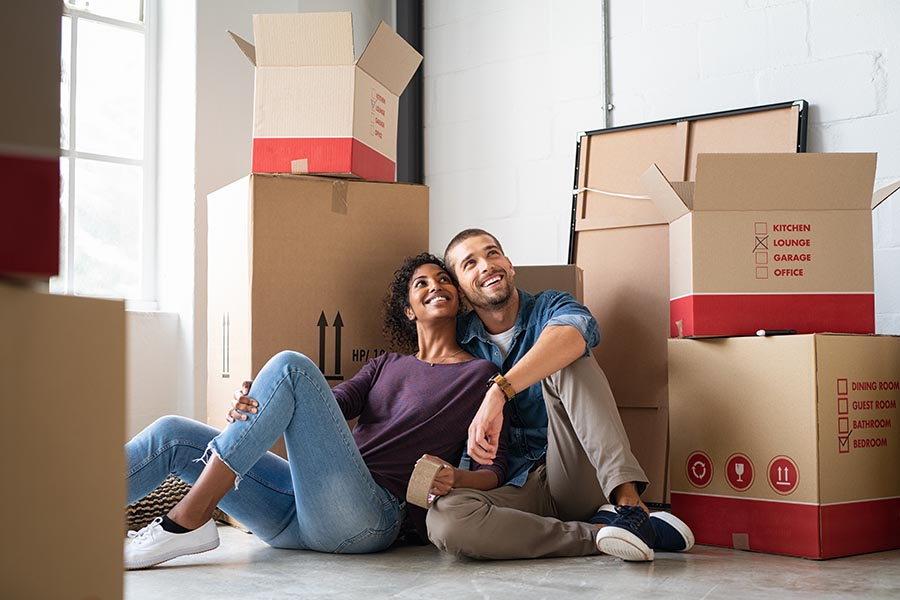 About Our Agency - Young Couple Sit Close Together Amongst Moving Boxes in Their New Home, Looking Proud