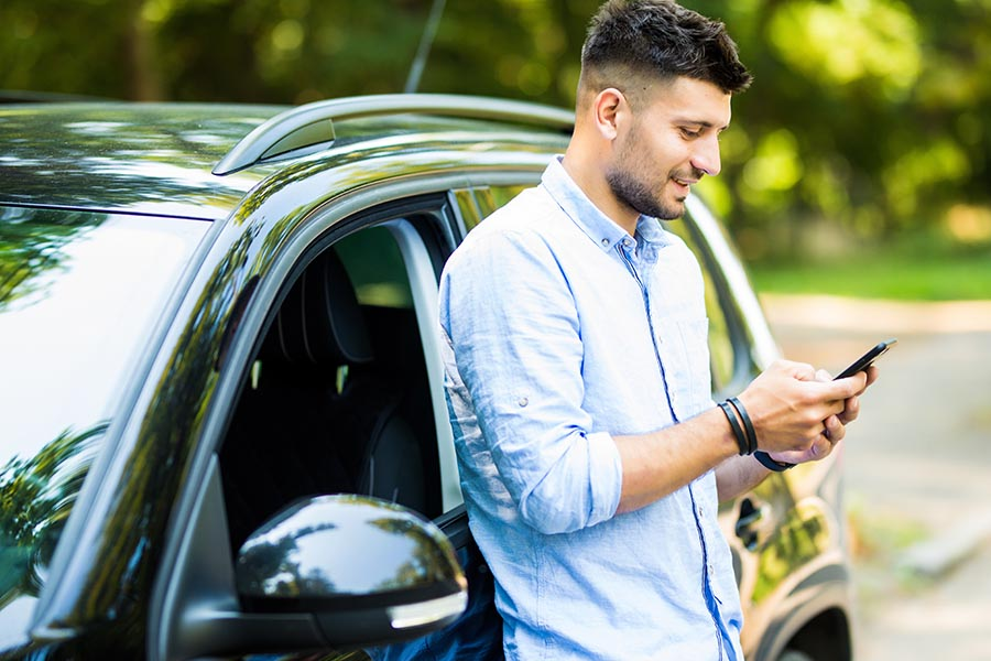 Client Center - Young Man Uses a Smartphone While Leaning Against a Car Parked On a Rural Road