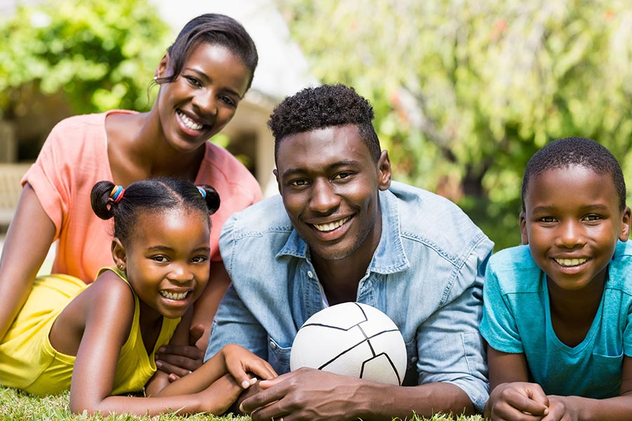 Personal Insurance - Family of Four Lays In the Grass With a Soccer Ball on a Sunny Day, All Wearing Brightly Colored Shirts