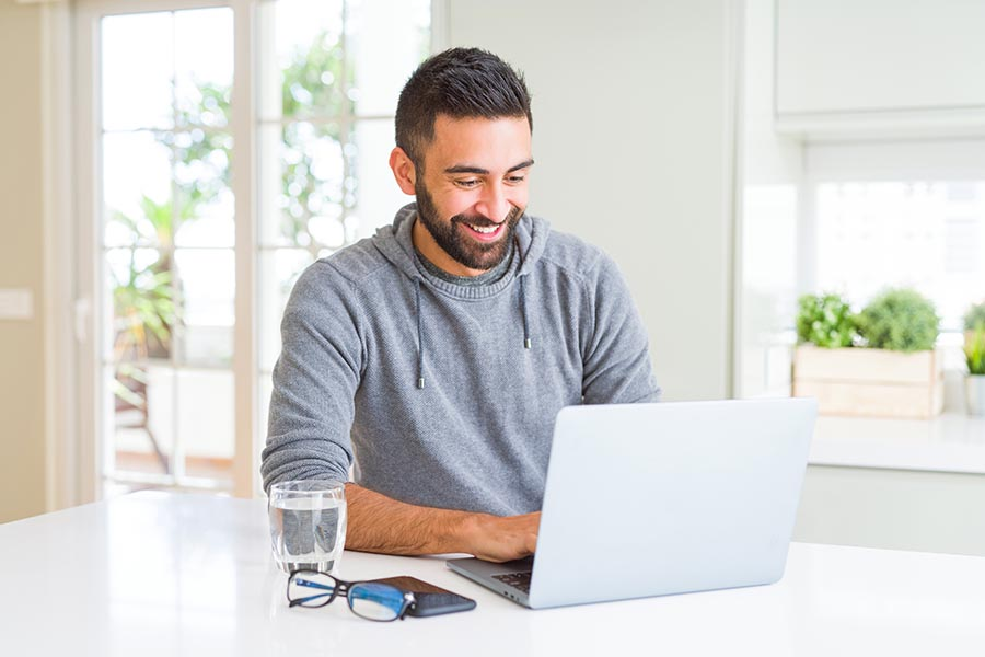 Resources - Young Man Smiles as He Uses a Computer in His Kitchen