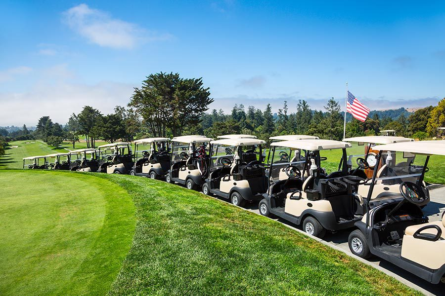 Specialized Business Insurance - Golf Carts Lined Up Outside Under the Sun, On a Path Overlooking a Golf Course